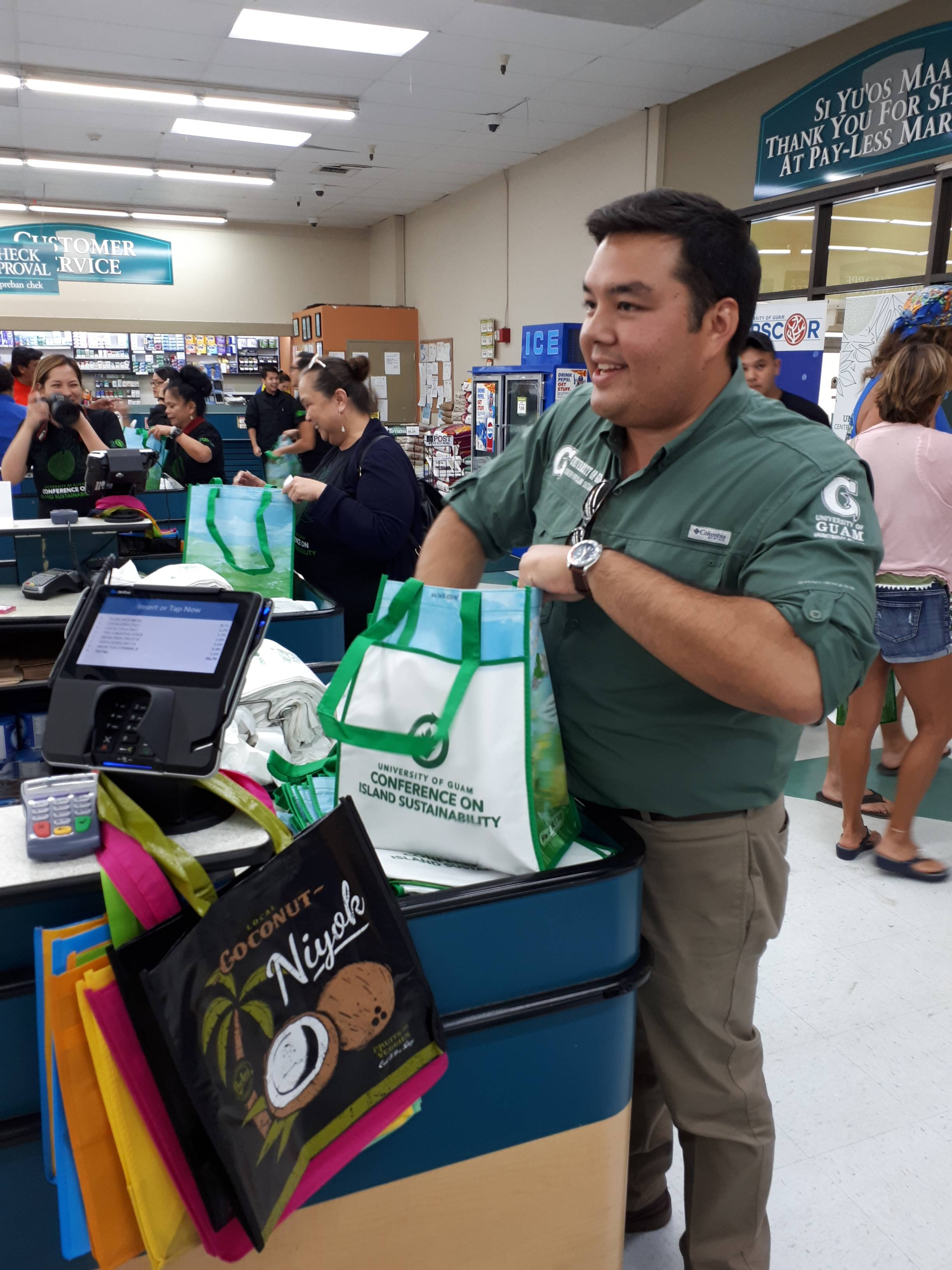 University of Guam Center for Island Sustainability (CIS) Executive Director Austin Shelton bags groceries in a free reusable bag for a customer on June 7 at the Agana Shopping Center Pay-Less Supermarket. CIS provided 500 free reusable bags in total to customers in the two days following the enactment of Public Law 34-110 banning plastic bags.