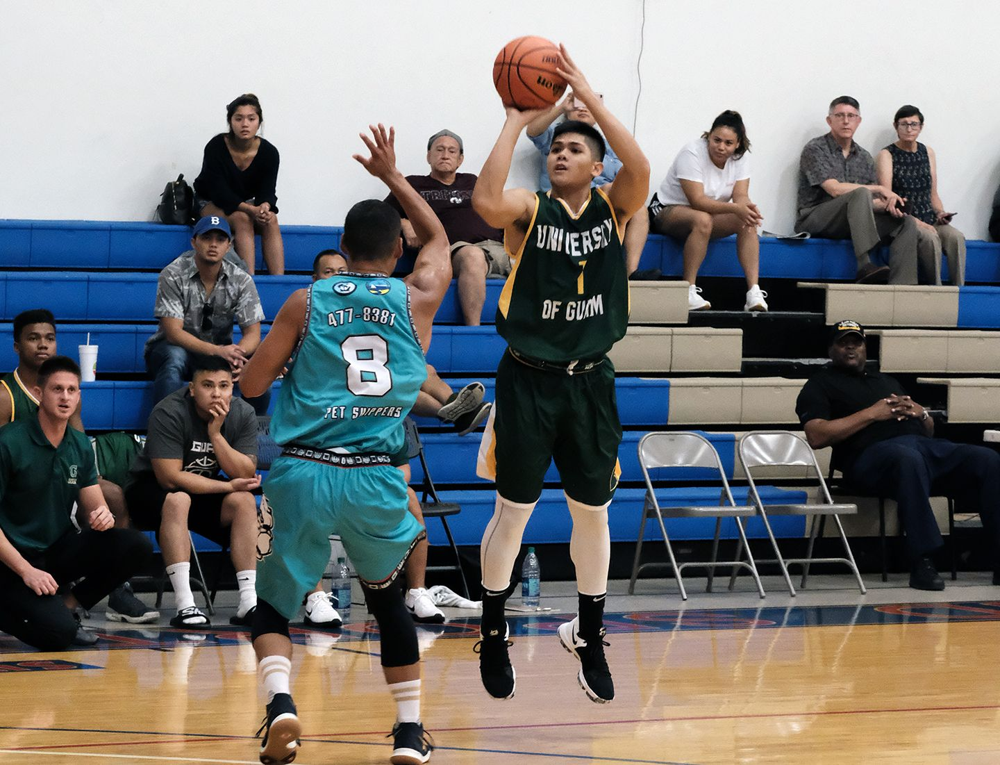 A.J. Carlos takes a shot against the Bulldogs in the previous UOG game as UOG President Thomas W. Krise and his wife, Patricia, watch in background.