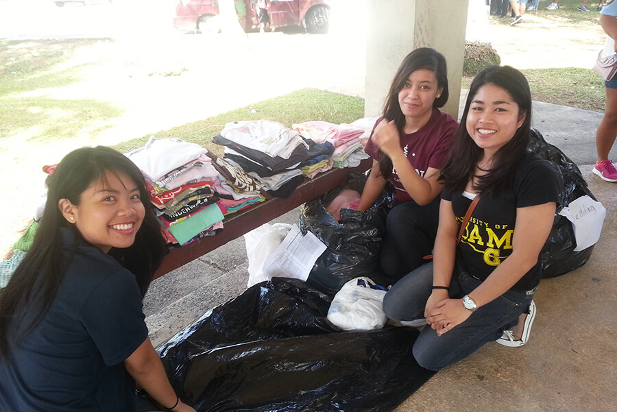 Students Hermi-Alyss Schacher, Vanessa Tudela, and Leizl Llegado distribute clothing