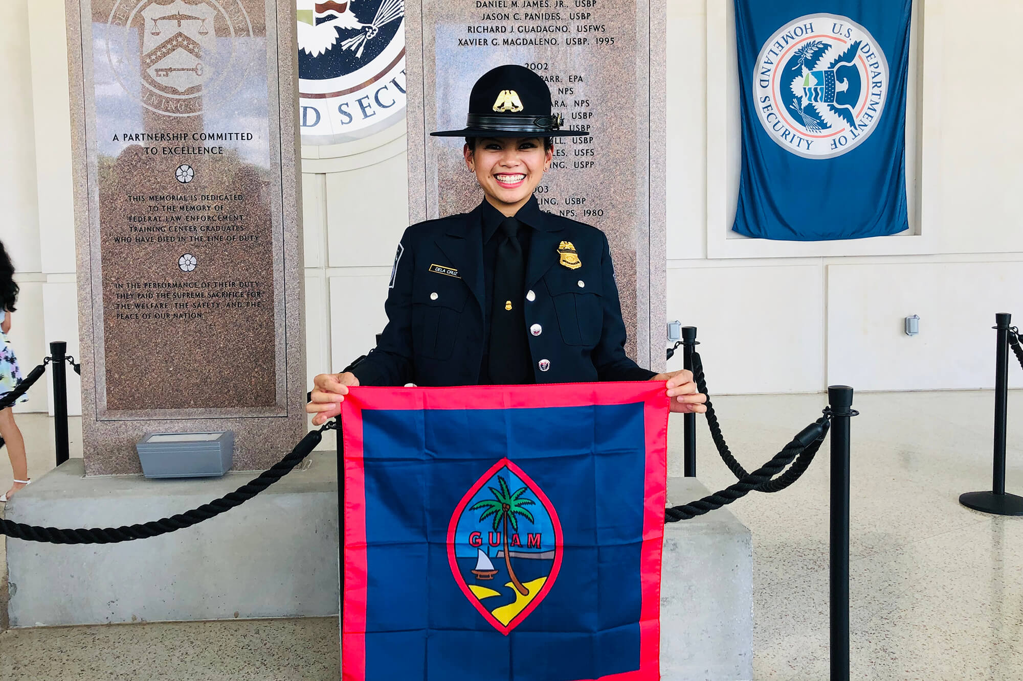 Kim Dela Cruz holds the Guam flag after her graduation