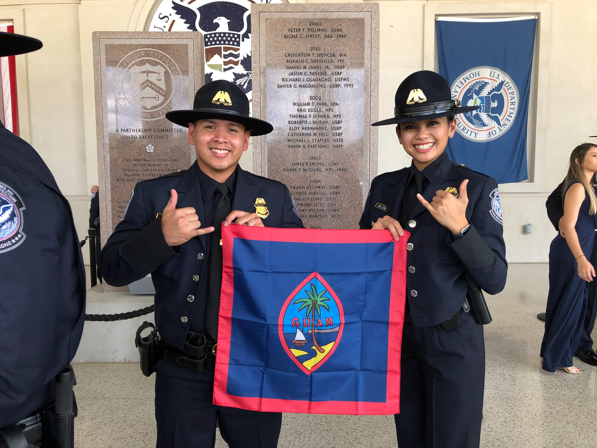 Kimberly Dela Cruz holds the Guam flag with fellow CBP graduate Roy Eay Jr. from Guam.