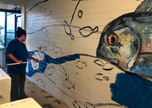 Micronesian studies graduate student Nina Peck works on an ocean-themed mural for the Marine Lab.