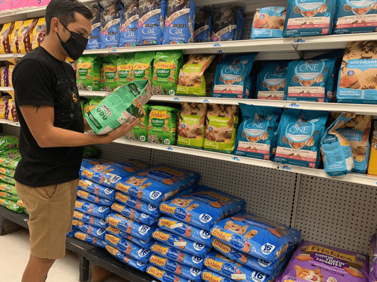 Photo of a someone picking out cat food