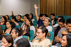 Photo of students raising up their hands in a lecture hall
