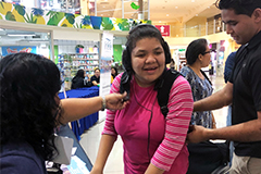 A CEDDERS staff member from UOG assists Jecilla Cruz trying out the SubPac